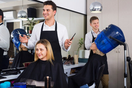 hairdressing saloon: Smiling positive young man cutting long hair of girl in hairdressing saloon