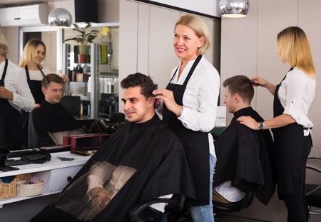 19's: Elderly blonde cutting hair of Indian guy in barbershop