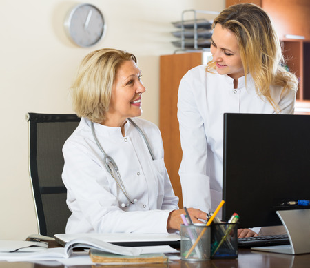 the elderly tutor: Two smiling female doctors in white overalls working together with computer at clinic Stock Photo
