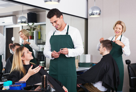 hairdressing saloon: Smiling young man cutting long hair of beautiful girl in hairdressing saloon