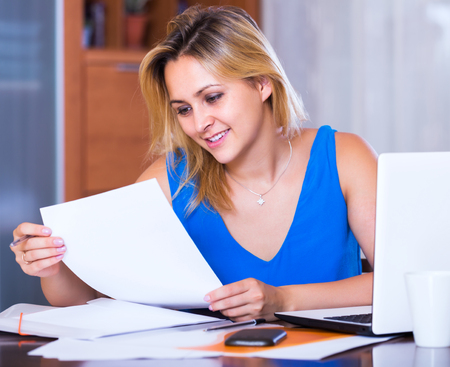 yuppie: Young blonde girl working with documents in office