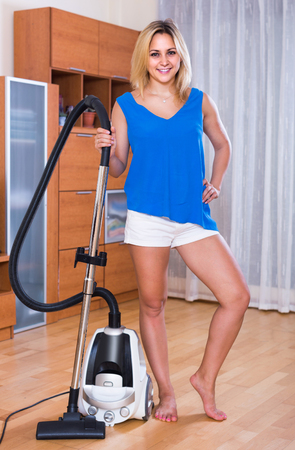 cleanup: Young american maid using modern hoover during clean-up indoors