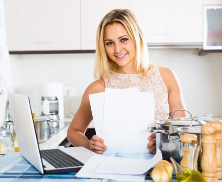 kitchen spanish: spanish blonde female signing documents at the kitchen