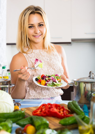 spanish girl: smiling spanish girl standing at kitchen table with plate of salad