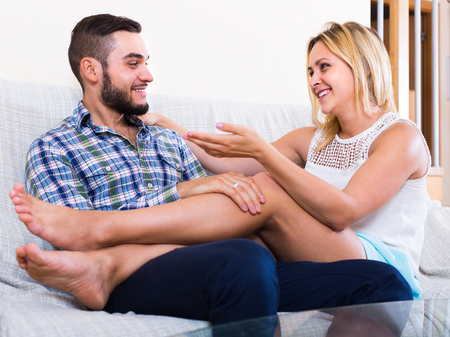 talkative: Happy smiling girl and her boyfriend having funny talk at home Stock Photo