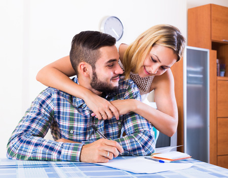 middle joint: Cheerful young couple at the table filling forms for joint banking account