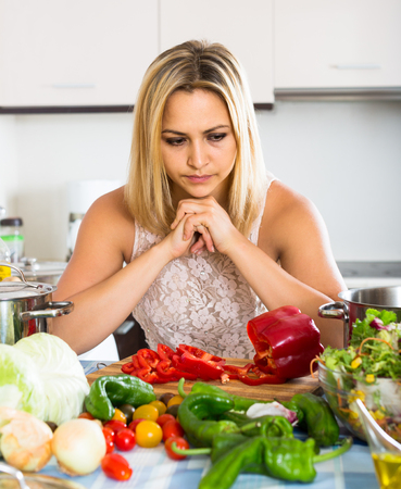 in low spirits: Tired young european  woman leaning her elbows at the kitchen