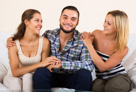 polygamy: Modern happy polygamous family with one husband and two wives Stock Photo