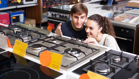 appliances: Young family couple choosing new gas-stove in appliances store Stock Photo