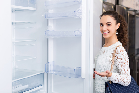 refrigerator kitchen: Cheerful young woman selecting domestic refrigerator in appliance store