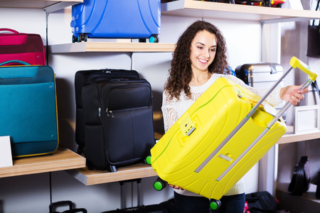 haberdashery: Young cheerful woman selecting travel suitcase in haberdashery shop