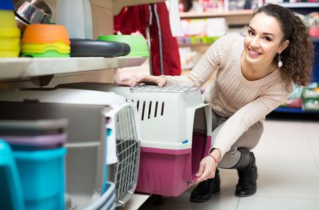 Gewone vrouwelijke klant koopt kennel voor gezelschapsdieren in de winkel