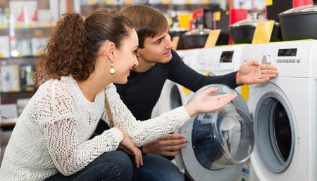 lavadora con ropa: Happy family couple buying new clothes washer in supermarket Foto de archivo