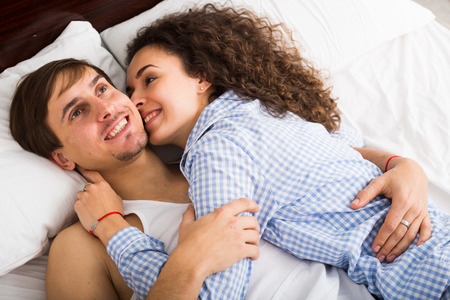 Happy man and woman lying in bed with smile Zdjęcie Seryjne