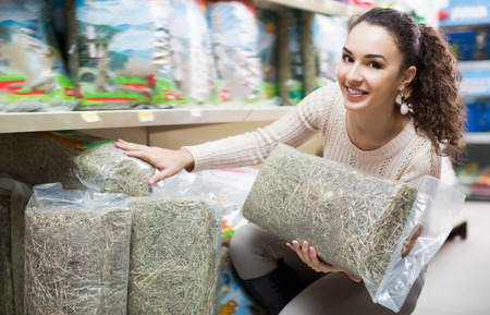 petshop: Brunette female customer buying feeding hay for pets in shop Stock Photo