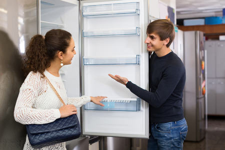 refrigerator: Middle class family couple choosing new refrigerator in hypermarket Stock Photo