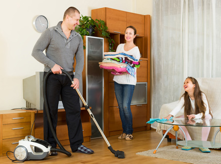 tidying up: Cheerful smiling family of three tidying up a room all together. Focus on man