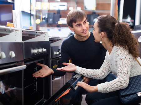 domestic appliances: Couple of young customers looking at build_in cookers in domestic appliances shop