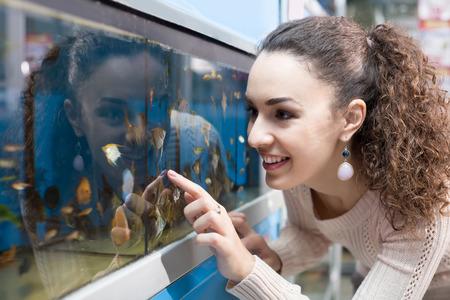 fish tank: smiling russian female customer watching tropical fish in aquarium tank