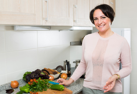 ama de casa: ama de casa de mediana edad preparar el calabacín en la cocina doméstica