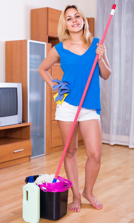 ordinary woman: Ordinary woman with mop and bucket in living room