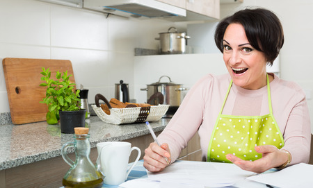 woman relax: Middle age woman filling banking documents and smiling in kitchen
