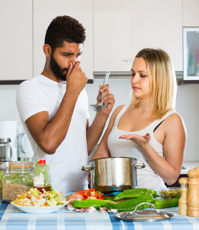 interracial family: Portrait of interracial family couple with stinking food in home kitchen