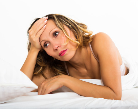 ennui: Sad female with head reclined upon hands in bedroom