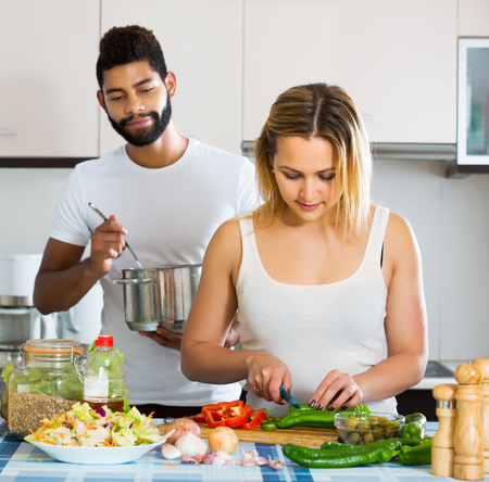 interracial couple: Positive young interracial couple cooking vegetables and laughing