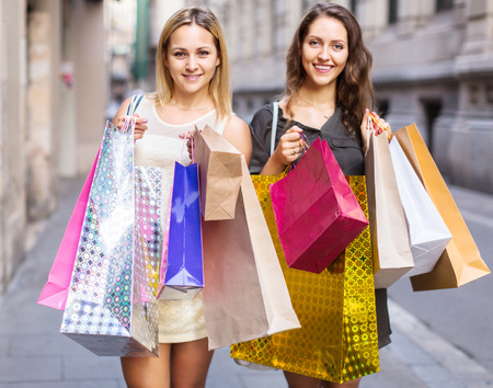 spendthrift: Laughing people carrying bags with purchases outdoors Stock Photo