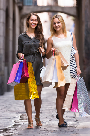 spendthrift: Two young smiling female friends with shopping bags at street