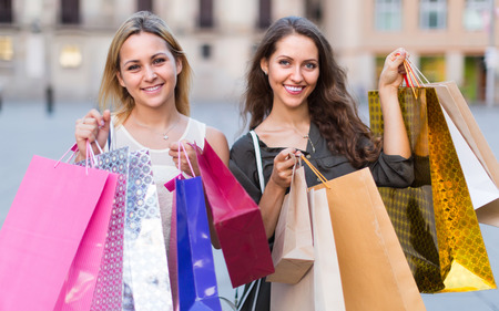 gladful: Portrait of two young women holding many bags after shopping Stock Photo