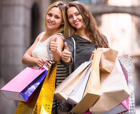 spendthrift: Portrait of two happy female friends with shopping bags at street