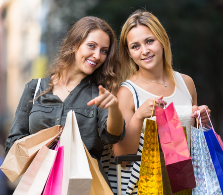 spendthrift: Portrait of two beautiful young women with shopping bags at street
