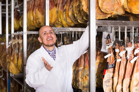 technologist: Middle age cheerful technologist with joints of serrano jamon at farm Stock Photo