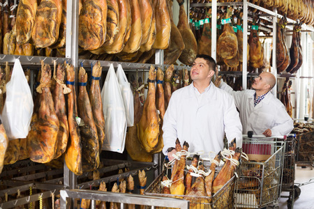 middle joint: Mature butcher and his assistant with the jamon joints at meat factory. Focus on young man Stock Photo
