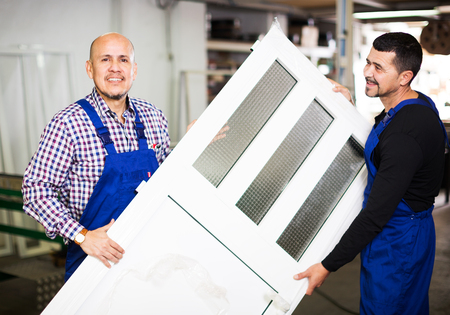 glasswear: workers with finished PVC profiles and windows at factory Stock Photo