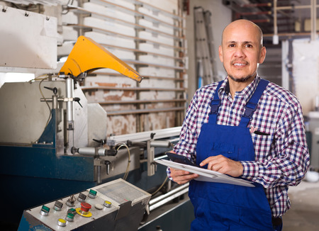 skilled operator: Portrait of professional worker in blue coverall at the work in PVC shop