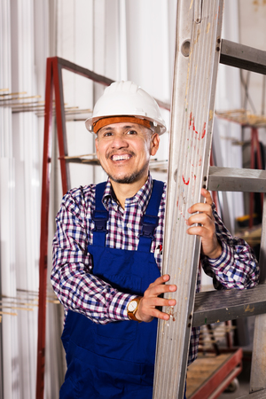 installer: Positive male installer in coverall working at construction site