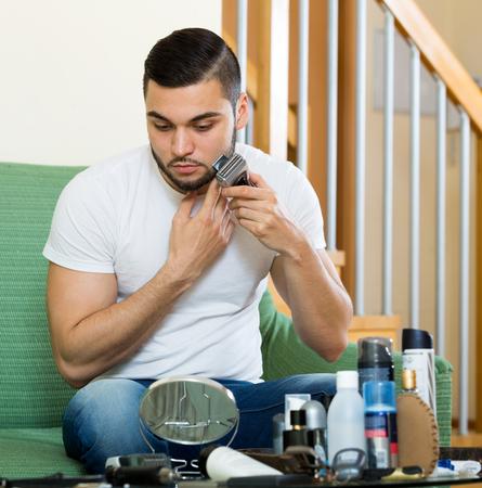 electric razor: Russian guy shaving face with electric razor Stock Photo