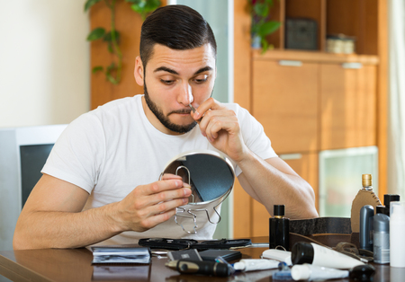 pincers: Handsome man remove hair from his nose with pincers at home Stock Photo