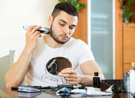 electric shaver: serious man shaving electric shaver at home in the living room Stock Photo