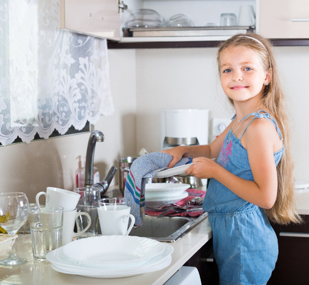 female child: Cheerful american female child cleaning dishware at home