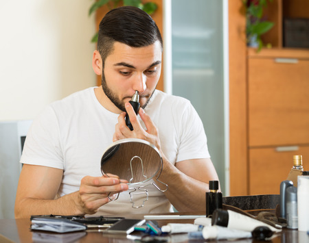 trimmer: Young man using trimmer for removing hair in his nose at home