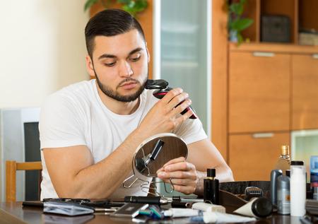 electric razor: European man shaving face with electric razor