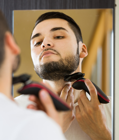 trimmer: adult man looking at mirror and shaving beard with trimmer Stock Photo