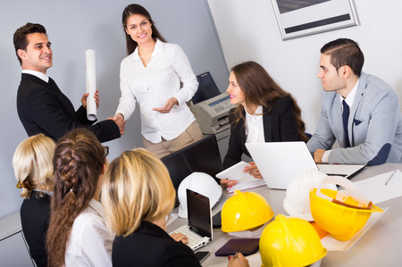 warmly: Professional team of constructors and designers warmly greeting new partner Stock Photo