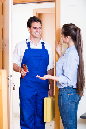 inviting: Young woman inviting handyman with tooling to come and help Stock Photo