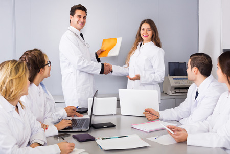 colloquium: Multinational happy interns and smiling adult professor cooperating at hospital meeting Stock Photo