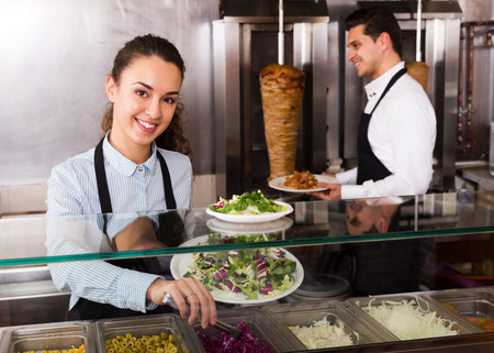 restaurant staff: Attractive restaurant staff posing at kebab counter and smiling
